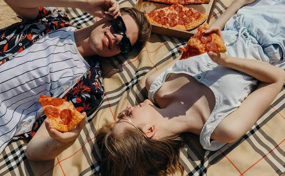 Normal_couple-laying-down-and-eating-pizza-4348786
